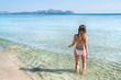 Young woman in bikini with her hand over head enjoying hot summer day on the beautiful Playa de Muro beach, Mallorca, Spain