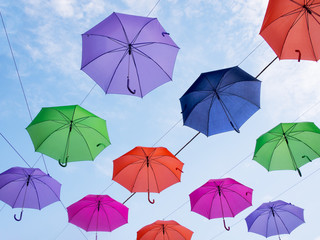 Umbrellas against blue sky.  Visible wires holding them.