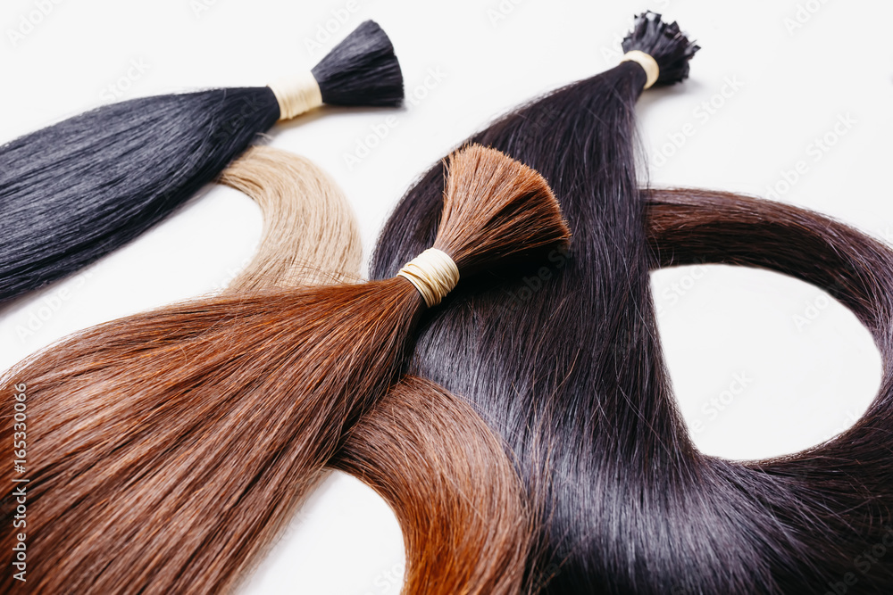 Fototapeta hair extensions of three colors on a white background. copyspace selective focus