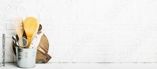 Zdjęcie XXL Kuchenne narzędzia, oliwna tnąca deska na kuchennej półce przeciw białemu ściana z cegieł. selektywne focus ..
