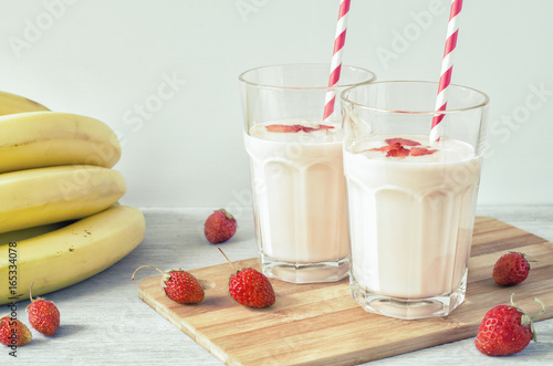 Foto op Aluminium Milkshake Two glasses of strawberry milkshake with a banana on a wooden board on a light background. Side view