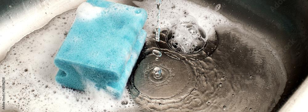 Fototapeta sponge in kitchen sink under dripping water, suitable for header or banner