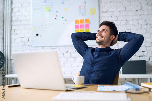 Smiling handsome businessman relaxing and enjoying coffee while taking break from work in office