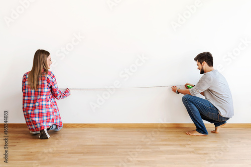 Obraz Couple in empty apartment measuring walls - fototapety do salonu