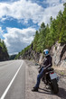Motorcycle driver resting on roadside on the mountain asphalt road at sunny day