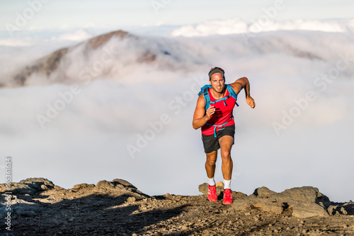 Fotografía  Runner trail running fitness man on endurance run - motivation and concentration on race in sky and clouds background on nature landscape