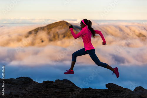 Fitness run athlete runner girl running at sunset on mountain trail Canvas Print