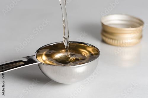 Fényképezés  Pouring White Wine Vinegar into a Teaspoon