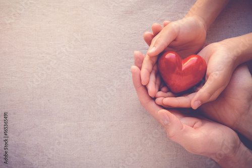 Láminas  adult and child hands holiding red heart, health care love and family concept