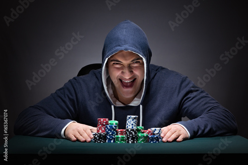 Fotografia Young man wearing a hoodie with cards and chips gambling