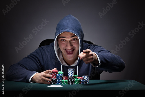 Papel de parede Young man wearing a hoodie with cards and chips gambling