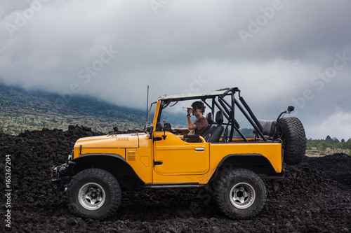 Fotografija A curly-haired man drinking water is sitting in the offroad yelow vehicle parked