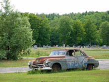 Old Rusty Car In Front Of A Cemetery