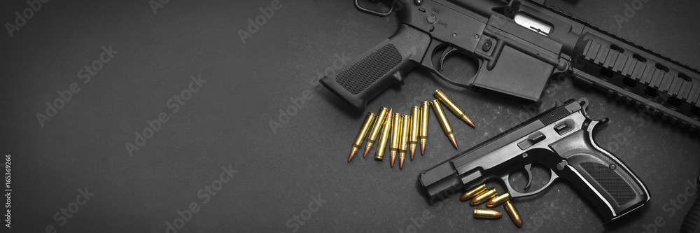 Fototapeta Handgun with rifle and ammunition on dark background with copy space
