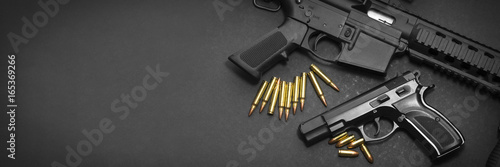 Valokuva Handgun with rifle and ammunition on dark background with copy space