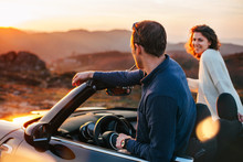 A Young Couple Have Fun In A Convertible At Sunset, Around Them Beautiful Nature