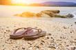 Violet flip flops against the sandy beach of the brown beach on weekends.