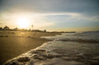 Beach sunset is a golden sunset sky with a wave rolling to shore as the sun sets over the ocean horizon