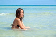 Young woman sitting in clear sea water of the beautiful Alcudia beach in Mallorca, Spain