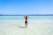Young woman in bikini standing in clear blue water on the beautiful beach of Alcudia, Mallorca, Spain