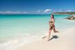Woman with sexy body in bikini running on beach