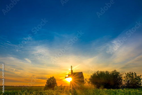 fototapeta na lodówkę Sunrise and an Old Wooden Windmill