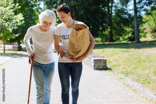 Incredible woman assisting elderly lady with her everyday routine Canvas Print