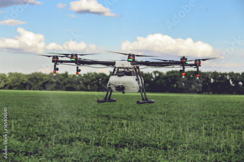 Professional large drone spray water over a green field. Agriculture industry concept drone with flying green field.