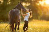 Fototapeta Konie - Young woman with her horse in evening sunset light
