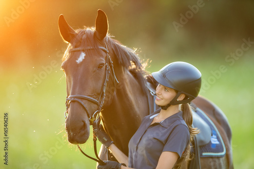 Fototapeta Young woman rider with her horse in evening sunset light obraz