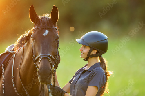 Valokuvatapetti Young woman rider with her horse in evening sunset light