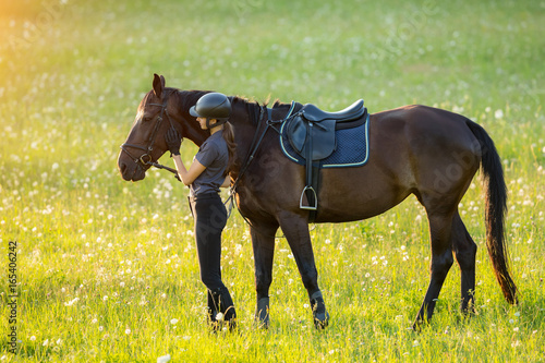 Valokuva  Young woman rider with her horse in evening sunset light