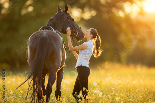 Photo  Young woman with her horse in evening sunset light