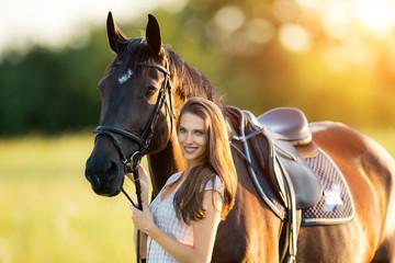 Młoda kobieta z koniem w wieczór zmierzchu świetle