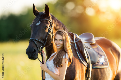 Valokuva  Young woman with her horse in evening sunset light