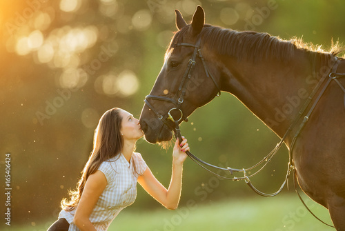 Young woman with her horse in evening sunset light Canvas-taulu