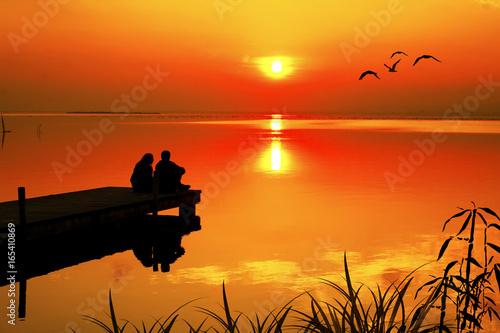 Foto auf AluDibond Pier enamorados mirando la puesta de sol