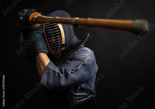 Man is practicing kendo martial arts in traditional armor .He swinging with bamboo sword shinai.