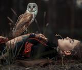 Dziewczyna kłama z sową na trawie w lesie. Zbliżenie. - 165418887