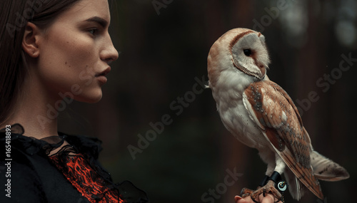 Photo  Portrait of girl with owl in hand. Close-up.
