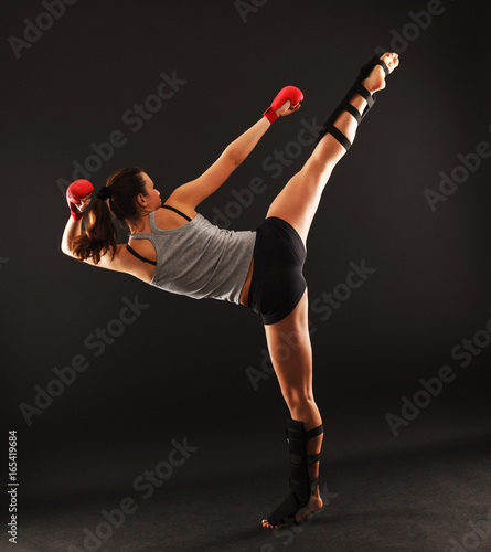 Staande foto Vechtsport Young attractive female martial arts fighter.High kick.
