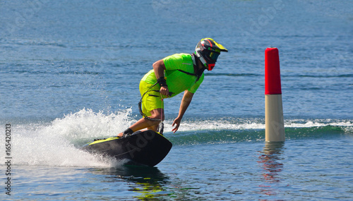Poster Nautique motorise Male Motosurf Competitor Taking corner at speed creating a lot of spray.