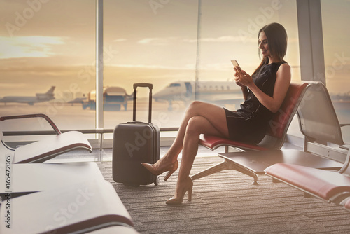 Gorgeous positive lady is checking news on smartphone