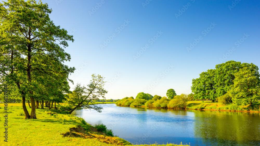 Sommerliche Landschaft mit Wiesen und Fluss