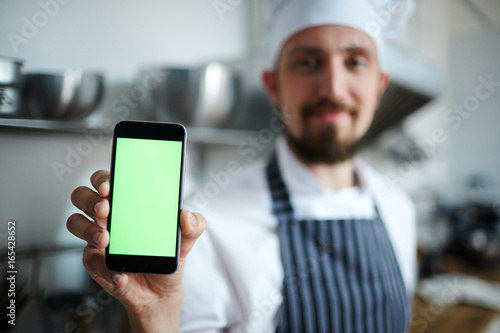 Chef showing new online recipe in smartphone