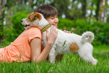Young Woman And Dog Lying On Green Grass, Hugging And Having Fun Together Outdoors