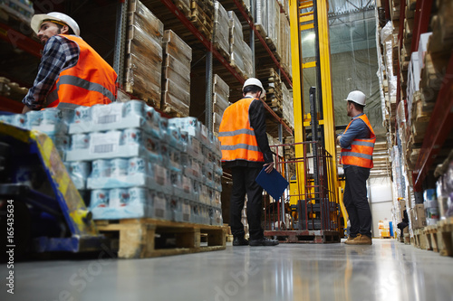 Photo  Group of several loaders working in warehouse aisle between tall racks, moving p