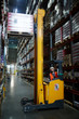 Portrait of warehouse worker using reach fork truck to load pallet with boxes on tall rack