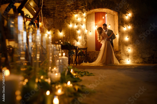 Photo Stylish hipster wedding couple in romantic loft decorations at night