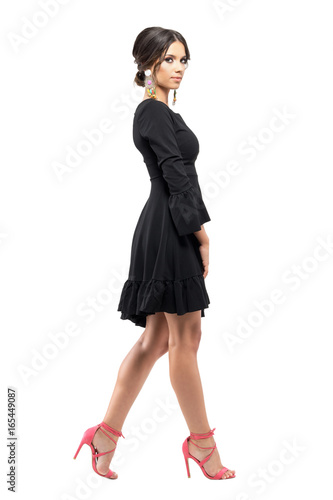 Fotografía  Profile of classy sophisticated woman in dress and sandals walking and looking at camera